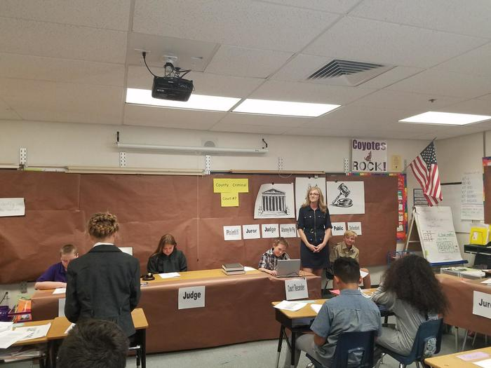 "Mrs. Cook looks on as the ""lawyers"" present the case"