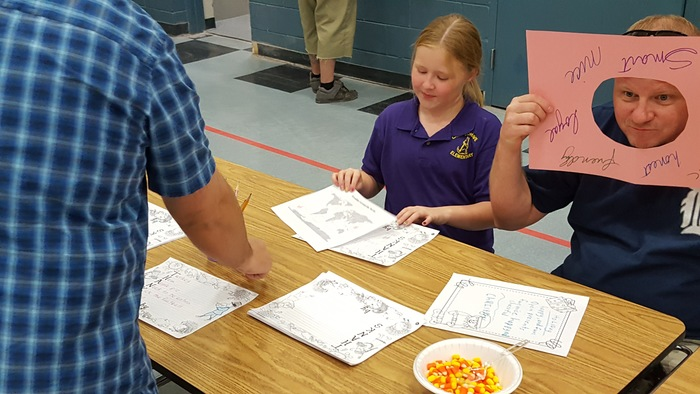 Grace and her dad complete activities during literacy night.