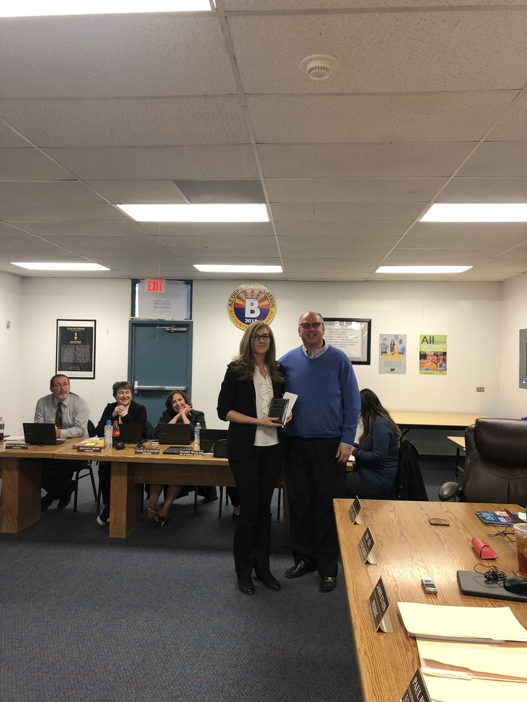 Mrs. Cook is presented with the McKellips Award by Mr. Crow at the February 4th school board meeting.